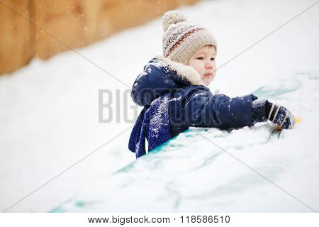 Little boy playing alone with toy in snow, close up. Outside, winter.