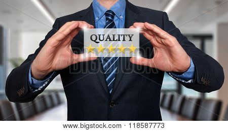 Businessman Holding White Card With Quality Five Stars Sign, Office - Stock Photo