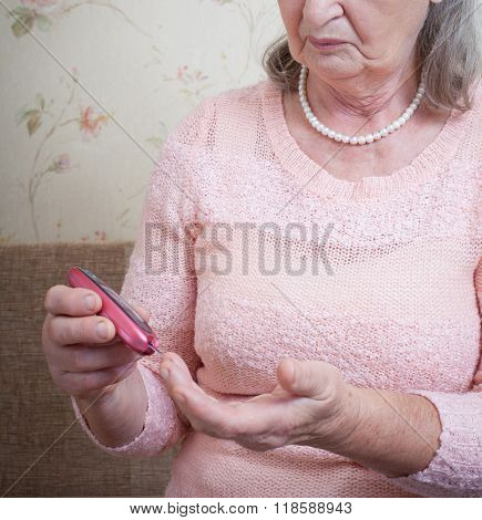 Elderly woman makes testing high blood sugar.