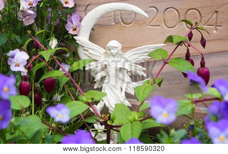 Grave Angel And Flowers In Front Of Grave Stones