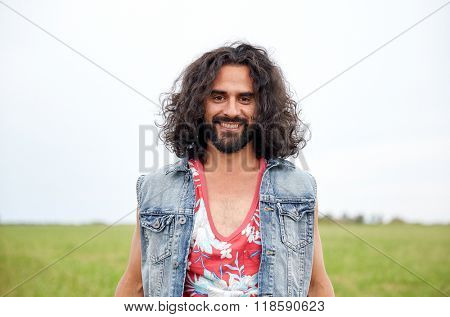 nature, summer, youth culture and people concept - smiling young hippie man in denim vest on green field
