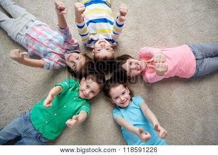 childhood, fashion, friendship and people concept - group of happy smiling little children lying on floor and showing thumbs up