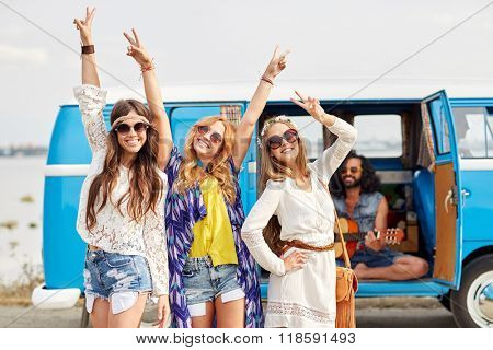 summer holidays, road trip, vacation, travel and people concept - happy young hippie friends having fun and dancing over minivan car
