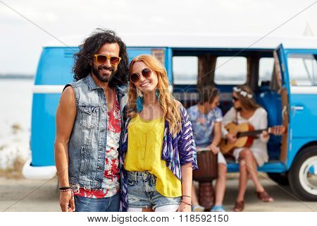summer holidays, road trip, vacation, travel and people concept - smiling young hippie couple with friends over minivan car