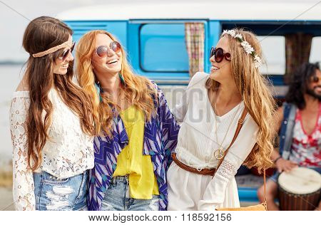 summer holidays, road trip, vacation, travel and people concept - happy young hippie friends having fun and talking over minivan car