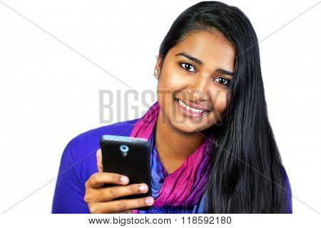 Young pretty india woman looking and smiling at camera, holding her smart-phone, on white background