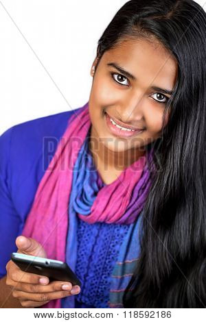 Young pretty india woman looking at camera, smiling,holding her smart-phone, vertical, white background