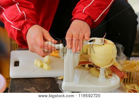 A blurred motion of women peeling apple skin spirally using apple peeler tool