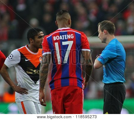 MUNICH, GERMANY - MARCH 11 2015: Referee William Collum gives Shaktar's  Douglas Costa  and Bayern Munich's Jerome Boateng a lecture followed by a yellow card during the UEFA Champions League match
