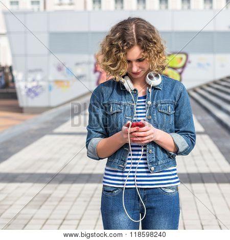 Young Hipster curly woman using her phone
