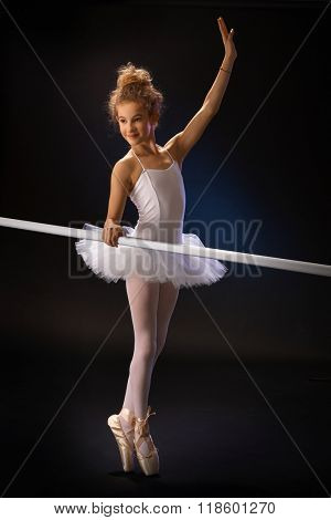 Young ballet student exercising by ballet bar over black background. Full size.