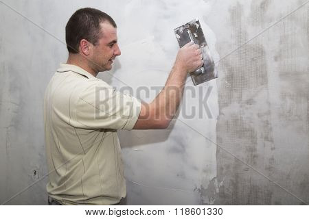 Man worker using float to apply first layer of putty