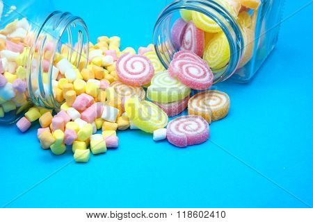 Colorful spiral jelly and colorful marshmallows with glass jars on blue background