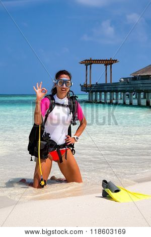 Female scuba diver on a beach is making the OK sign