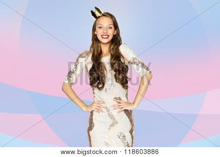 people, holidays and celebration concept - happy young woman or teen girl in party dress and princess crown over pink violet background