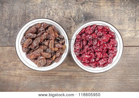 Dried Cranberries And Raisins In Bowls On Wooden Background