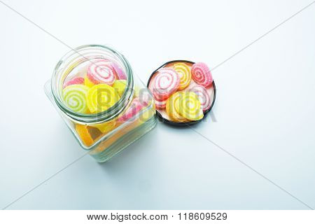 Colorful spiral jelly with glass jars on gray background. Focus on jelly on black lids. Space for te