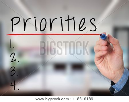 Business Man Hand Writing Priorities List With Marker Isolated On Office
