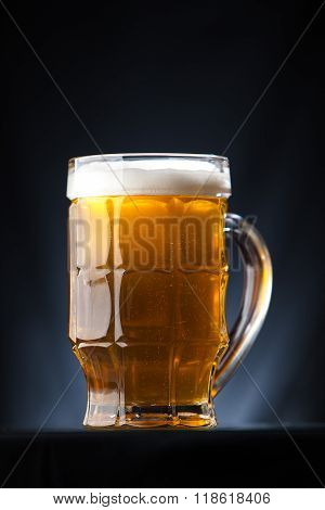 Big glass of beer over a dark background
