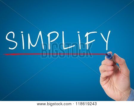 Businessman Hand Writing Simplify With Marker On Transparent Wipe Board Isolated On Blue