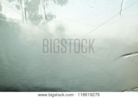 Blurred of outside view through car window with water drops and curtain.