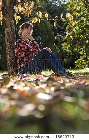 Thoughtful Young Woman Sitting Under An Autumn Khaki Tree