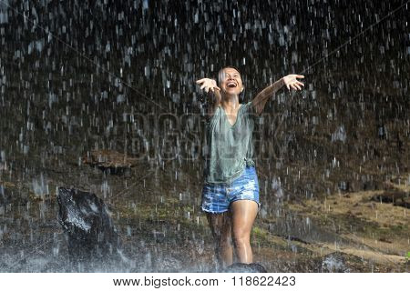 Happy woman enjoying water falling from tropical waterfall, Thailand