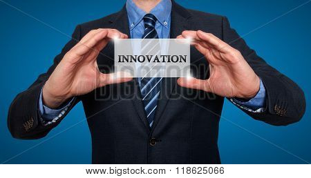 Businessman Holding White Card With Innovation Sign, Blue - Stock Photo