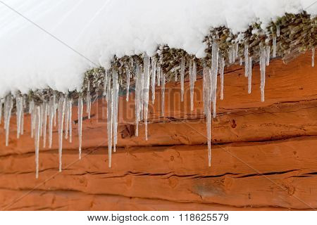 Isicles Hanging From A Snowy Roof On A Red Barn