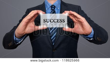 Businessman Holding White Card With Success Sign, Grey - Stock Photo