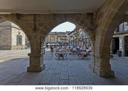 Guimaraes, Portugal - October, 2015: People enjoying the esplanades in the Oliveira Square, seen through the old Town-Hall arcade. UNESCO World Heritage Site.