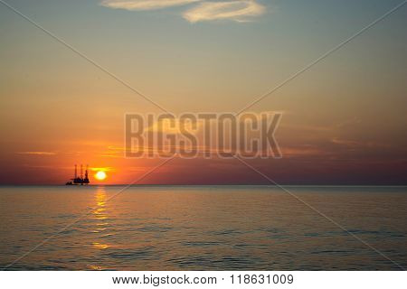 oil platform against beautiful sea sunset