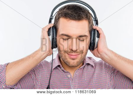 Smiling Man Listening Music In Headphones With Closed Eyes