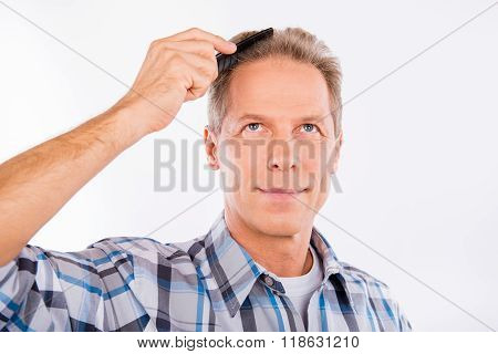 Handsome Cheerful Aged Man Combing His Hair