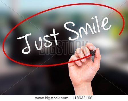 Man Hand Writing Just Smile With Black Marker On Visual Screen