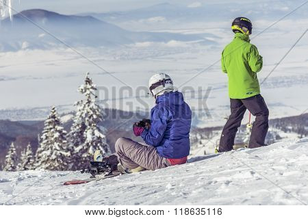 Snowboarders Sitting On The Sky Slope