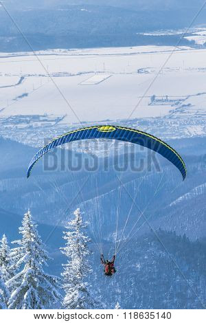 Paragliding Instructor Flying In Tandem Over The Mountains