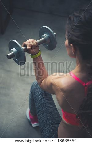 Seen From Behind Fitness Woman Lifting Dumbbell