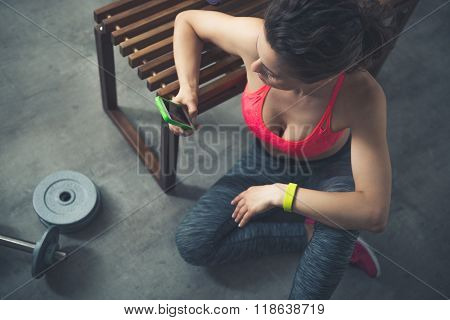 Fitness Woman Sitting In Loft Gym With Cell Phone