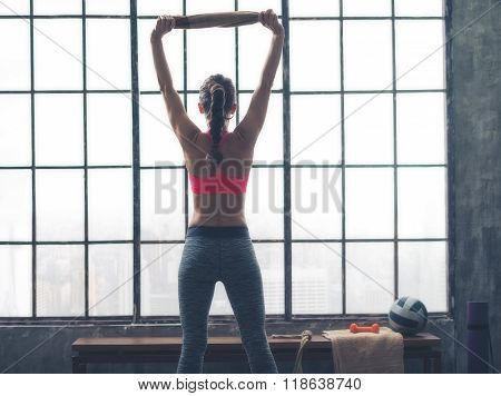 Seen From Behind Fitness Woman With Towel In Loft Gym