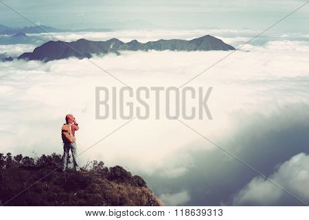 young woman hiker hiking on mountain peak