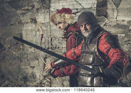 Old Knight With The Sword Is Protecting His Squire