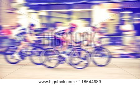 blurred image of a pack of bicycle riders rounding a corner in a bike race toned with a retro vintage instagram filter app or action effect