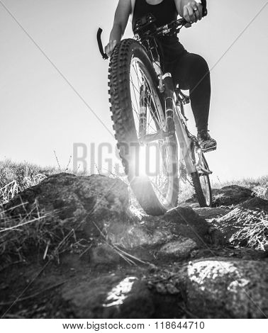a woman racing a bicycle down a dirt trail with big rocks in the back country to get away from the city toned with a retro vintage instagram filter app or action effect - cycling sport
