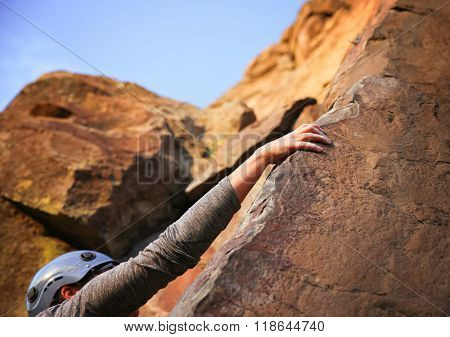 a close up of a woman rock climbing on a sheer cliff outdoor with a blue helmet on for safety