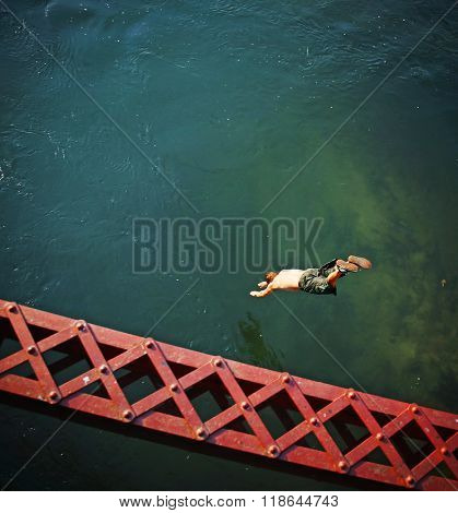 a boy diving  off an old train trestle bridge into a river toned with a retro vintage instagram filter effect