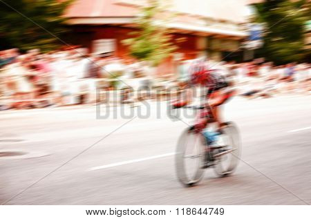 blurred image of a bicycle rider rounding a corner in a bike race toned with a retro vintage instagram filter app or action effect