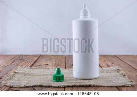 White Plastic Bottle Mock Up On Wood Background. Liquid Lens