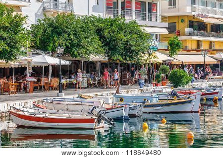 View on promenade with tourists  and color boats at Aghios Nikolaos port