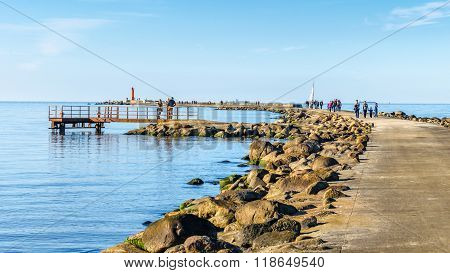 People walk on promenade at Mangalsala and visit red lighthouse, located at Riga sea port,